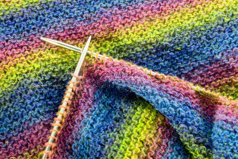 Colorful stripes knitted wool with needles background texture close-up. stock photo
