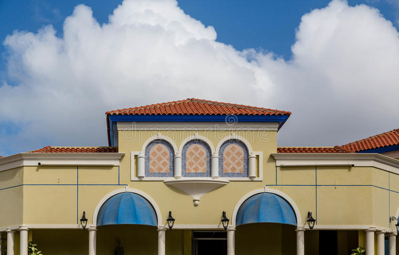 Colorful Stucco Building in Aruba. A colorful stucco building with a red tile roof in Aruba royalty free stock photography