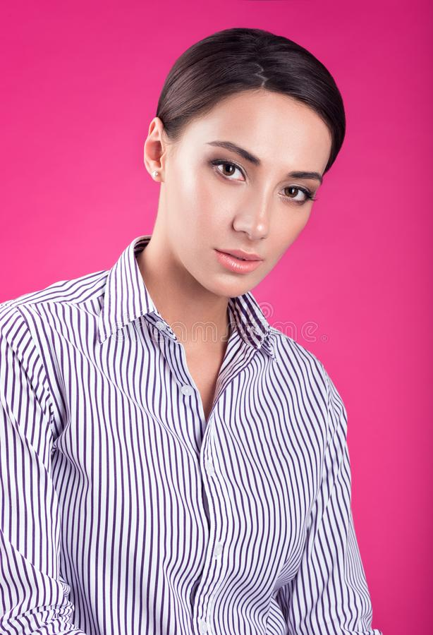 Colorful studio portrait of young attractive woman with a neutral expression. White striped shirt, bright pink background royalty free stock photos