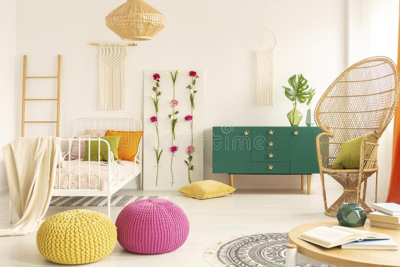 Colorful and stylish boho kid`s bedroom with peacock chair, single metal bed and green wooden cabinet stock photography