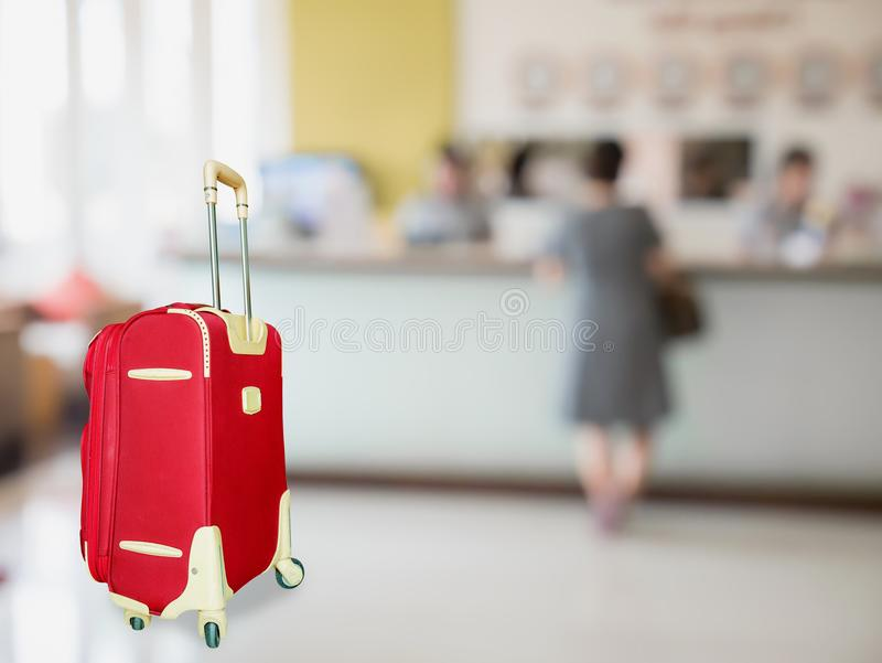 Colorful suitcase with hotel lobby. Blur background, travel concept royalty free stock photography