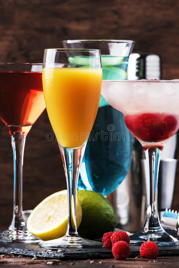 Colorful summer cocktails. Cold alcoholic beverages and drinks: mimosa, cosmopolitan, raspberry margarita and blue hawaii on. Wooden table background with bar royalty free stock photos
