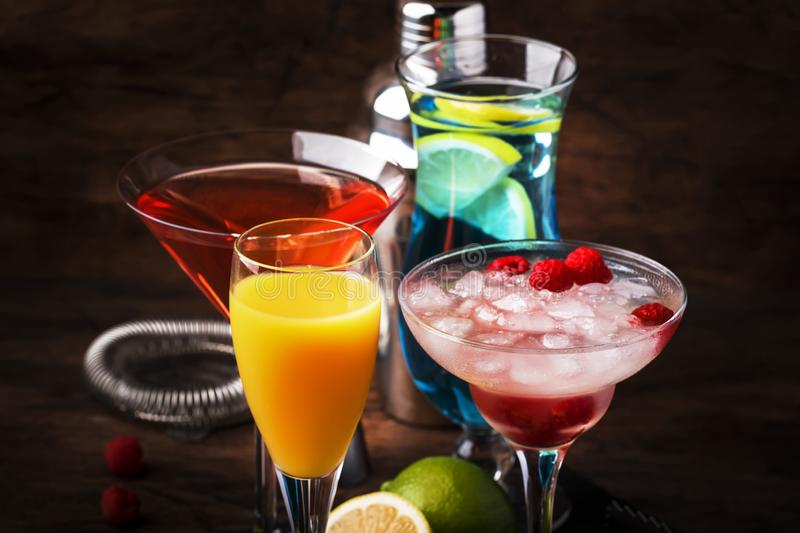 Colorful summer cocktails. Cold alcoholic beverages and drinks: mimosa, cosmopolitan, raspberry margarita and blue hawaii on royalty free stock photo