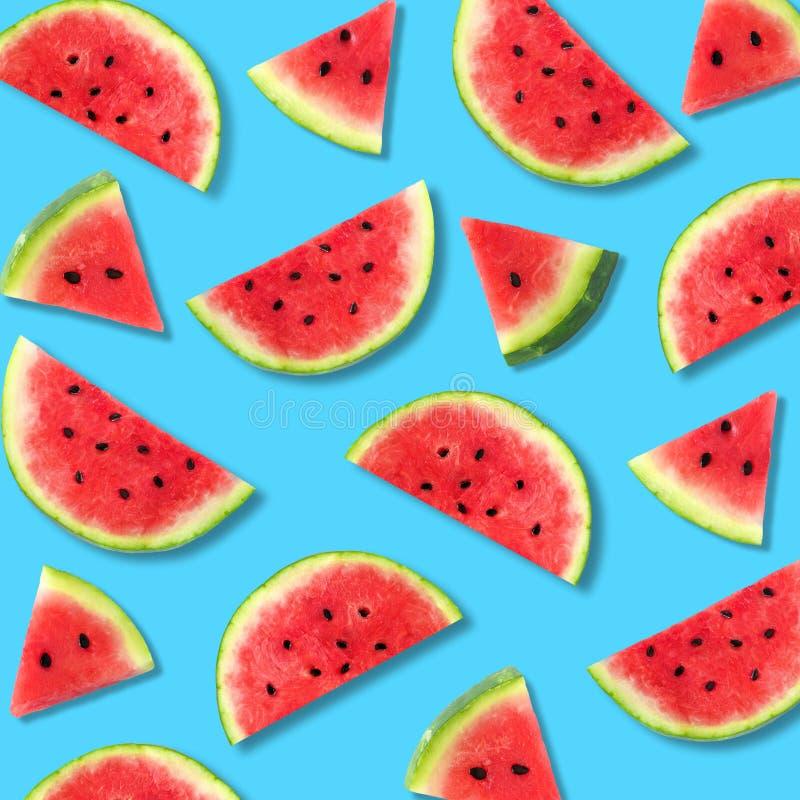 Watermelon slice summer fruit pattern on a blue background. Colorful summer fruit pattern of watermelon slices on a blue background stock images