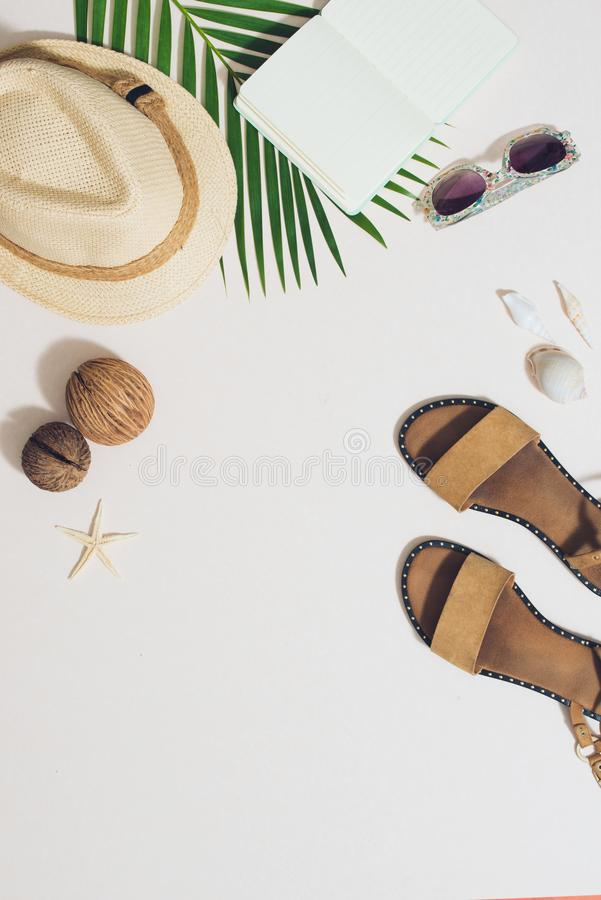 Colorful summer holidays fashion flat lay - straw hat, camera, sunglasses, sea shells on ligh background royalty free stock photography