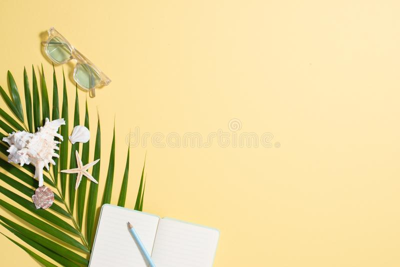 Colorful summer holidays fashion flat lay - straw hat, sunglasses, sea shells on bright yellow background royalty free stock images