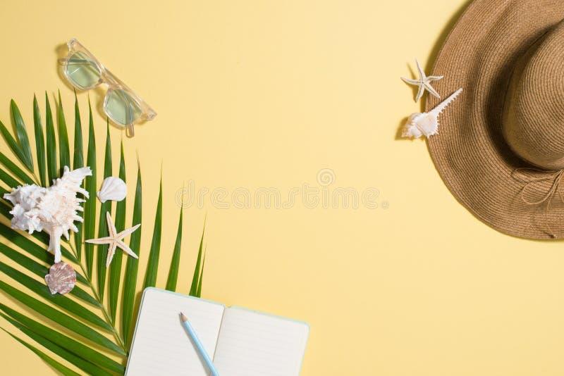 Colorful summer holidays fashion flat lay - straw hat, sunglasses, sea shells on bright yellow background.  royalty free stock photo