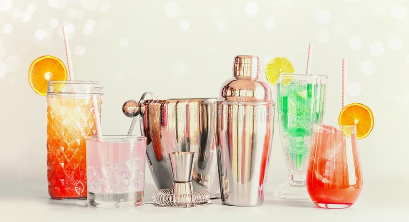 Colorful summer long drinks bar and cocktails tools in various glasses with drinking straws and citrus fruits standing at light stock photography