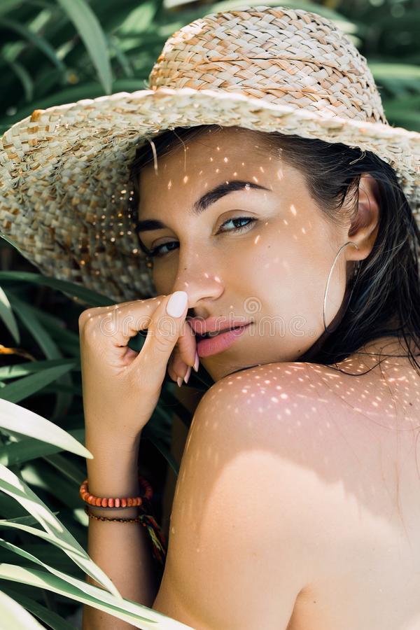 Colorful summer portrait of young attractive brunette woman wearing sunglasses under a palm tree by the swimming pool royalty free stock photo