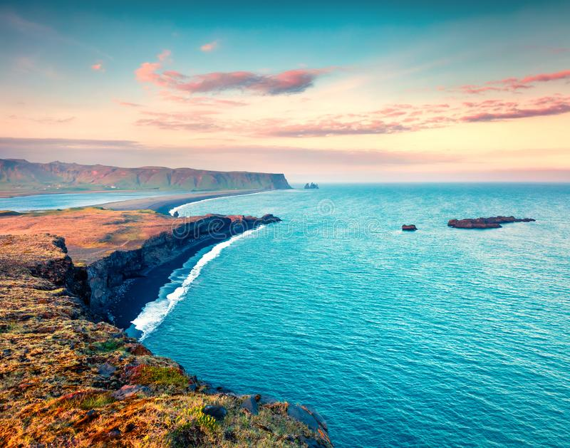 Colorful summer sunset on the Kirkjufjara beach. Evening view of Reynisdrangar cliffs from Dyrholaey peninsula in Atlantic ocean. South Iceland, Vic village royalty free stock images