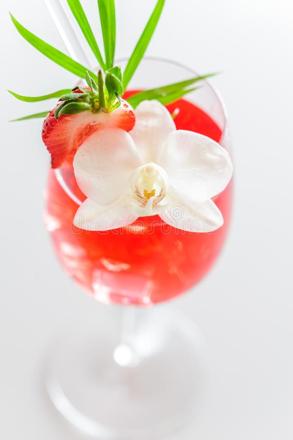 Colorful summer tropical cocktail in a glass with ice cubes, slice of strawberry and a tropical flower. Close up. royalty free stock photos
