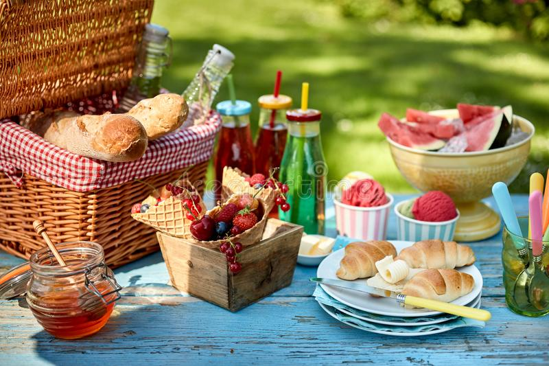Fruit, bread, honey and ice cream on picnic table stock images