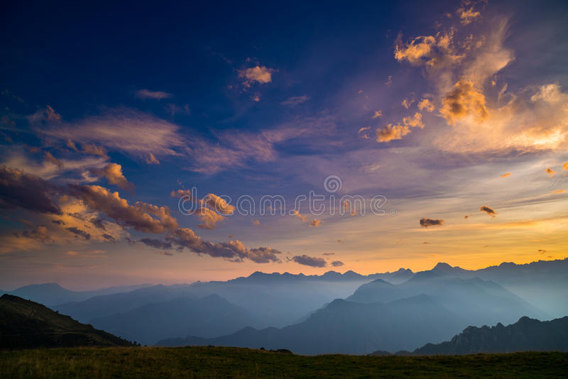 Colorful sunlight on the majestic mountain peaks, green pastures and foggy valleys of the Italian Alps. Golden cloudscape at sunse royalty free stock images