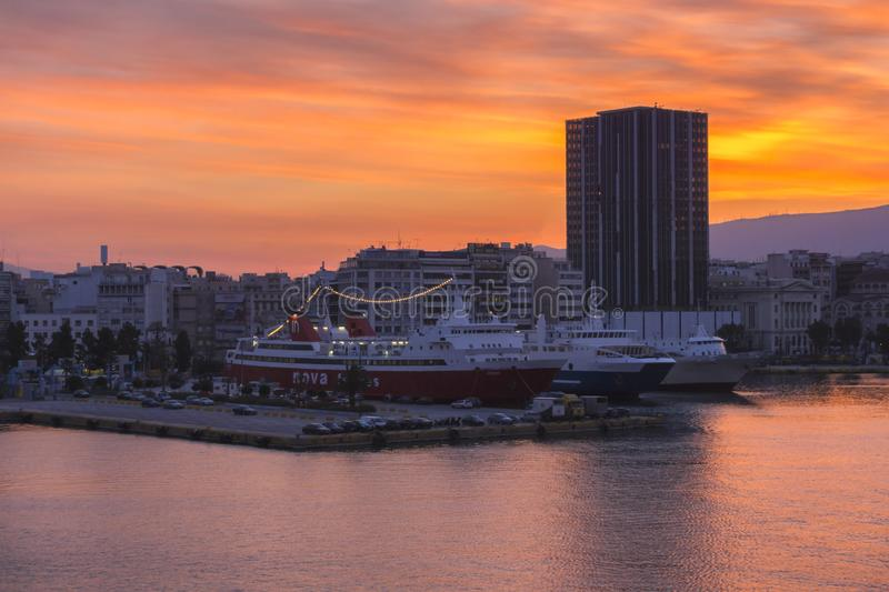 Colorful sunrise with fiery sky over the Piraeus port and city. Passenger vessels are docked at the jetty of the port royalty free stock photo
