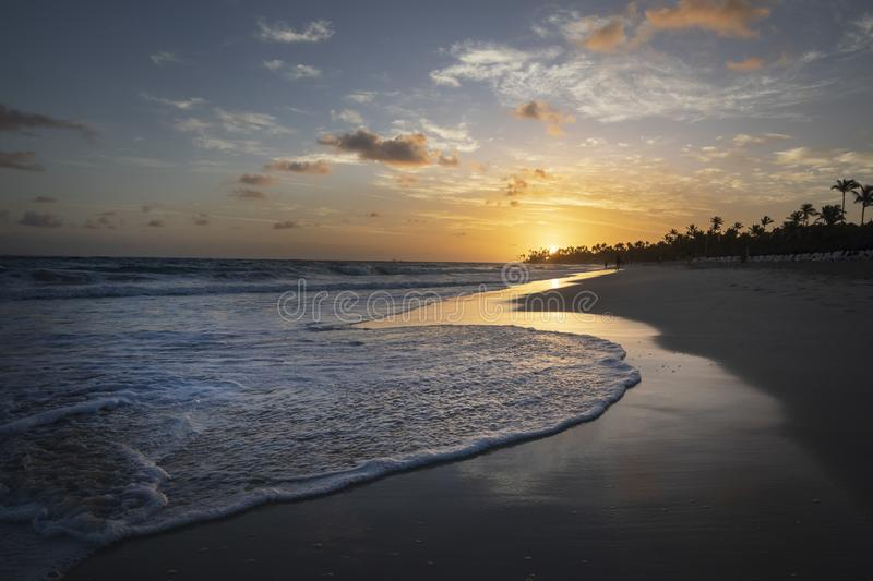 Sunrise over resort beach in Dominican Republic with couple walking in distance. stock images