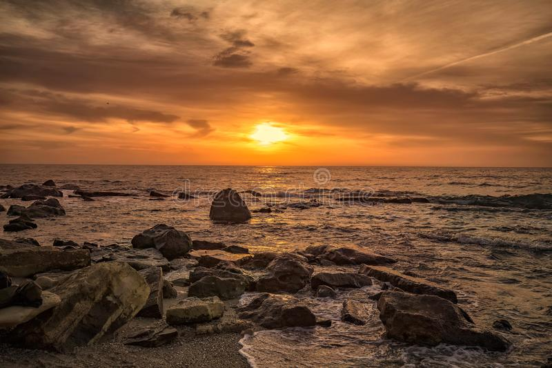 Sunrise over the sea with rocky coast royalty free stock image