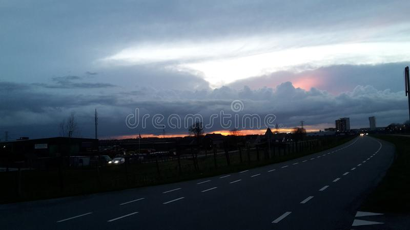 Colorful sunset behind thick cloud area above Rotterdam Nesselande in the evening stock image