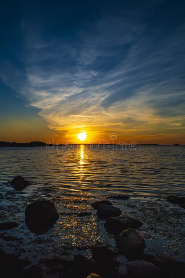 Colorful sunset by the calm sea. Beautiful shining light and reflections on the water in the dark evening. Coastal environment, magical atmosphere royalty free stock images