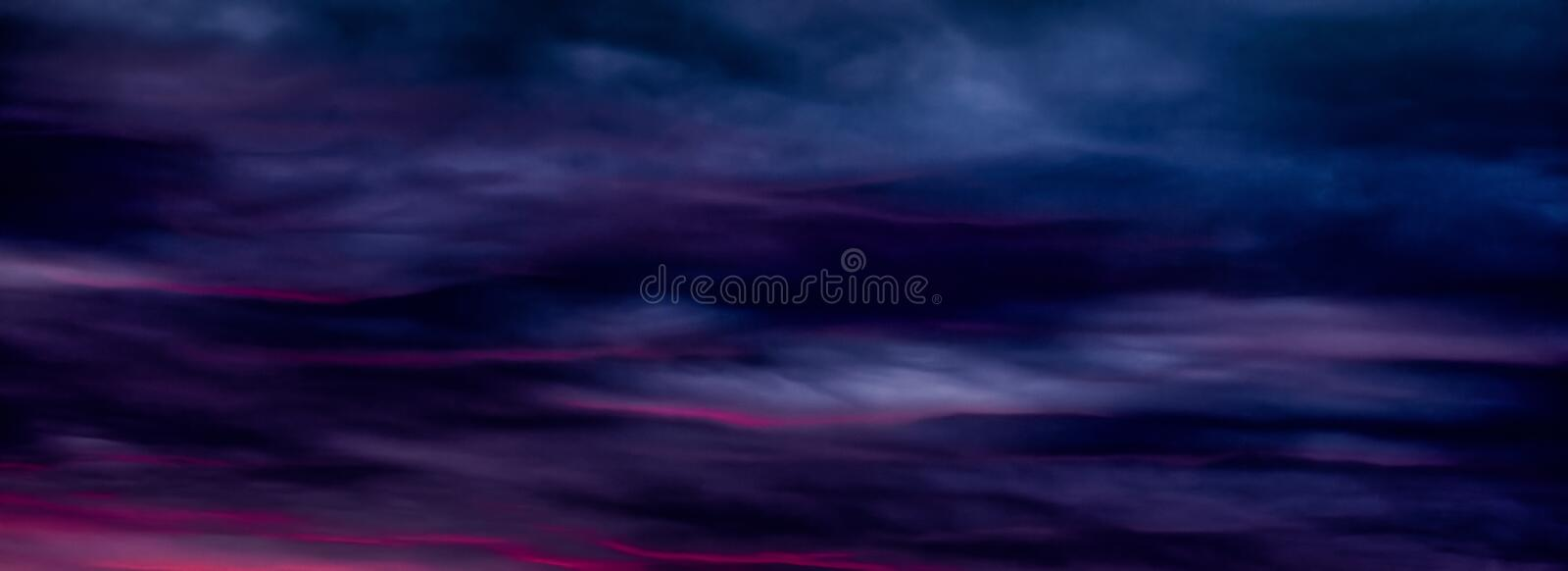 Colorful sunset with clouds in the evening. Abstract nature background. Dramatic and moody pink, purple and blue cloudy sunset sky.  stock photo