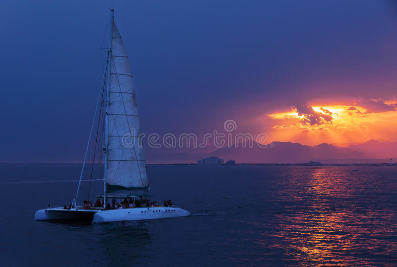 Colorful sunset. Dramatic and Atmospheric landscape. Costa Brava, Spain. Seacoast. Seascape with sailboat. Tourist catamaran. Sunset on the coast Almadrava stock photography