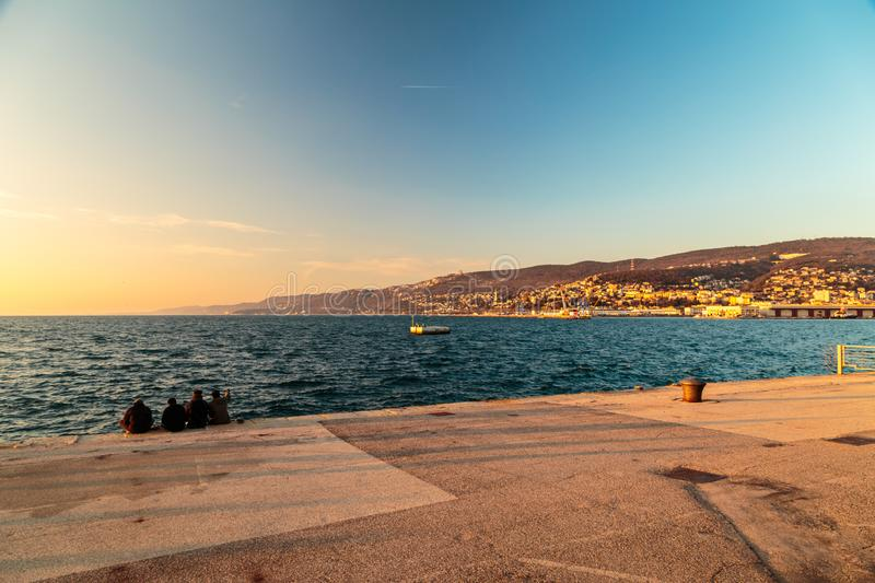 Colorful sunset in front of the city of Trieste. Winter evening in the gulf of Trieste royalty free stock photo