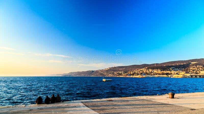 Colorful sunset in front of the city of Trieste. Winter evening in the gulf of Trieste royalty free stock image
