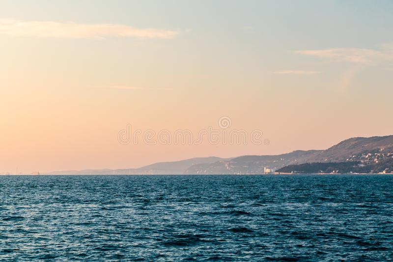 Colorful sunset in front of the city of Trieste. Winter evening in the gulf of Trieste stock image