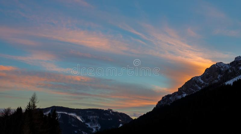 Colorful sunset with glowing clouds above mountain tops in the austrian alps in winter. In late fall royalty free stock photos