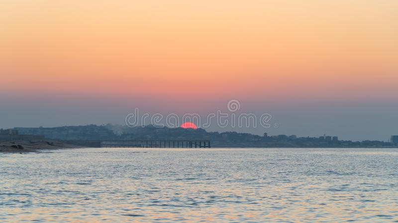 Colorful sunset over the coastal city royalty free stock images