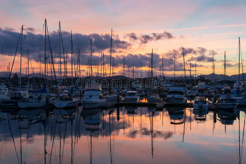 Colorful sunset over Coffs Harbour marina with yachts and boats royalty free stock photos