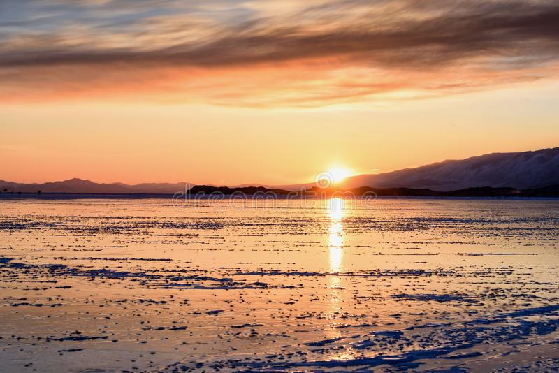 Colorful sunset over the crystal ice of Baikal lake. In winter stock photo