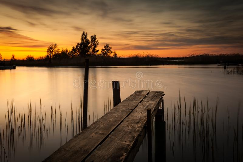 Sunset over lake in Finland. A colorful sunset over a lake with a small jetty in Finland royalty free stock photos