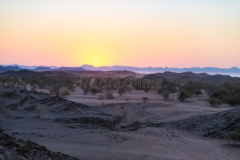 Colorful sunset over the Namib desert, Namibia, Africa. Mountains, dunes and Acacia trees silhouette in backlight. Orange red clea. R sky at the horizon stock image