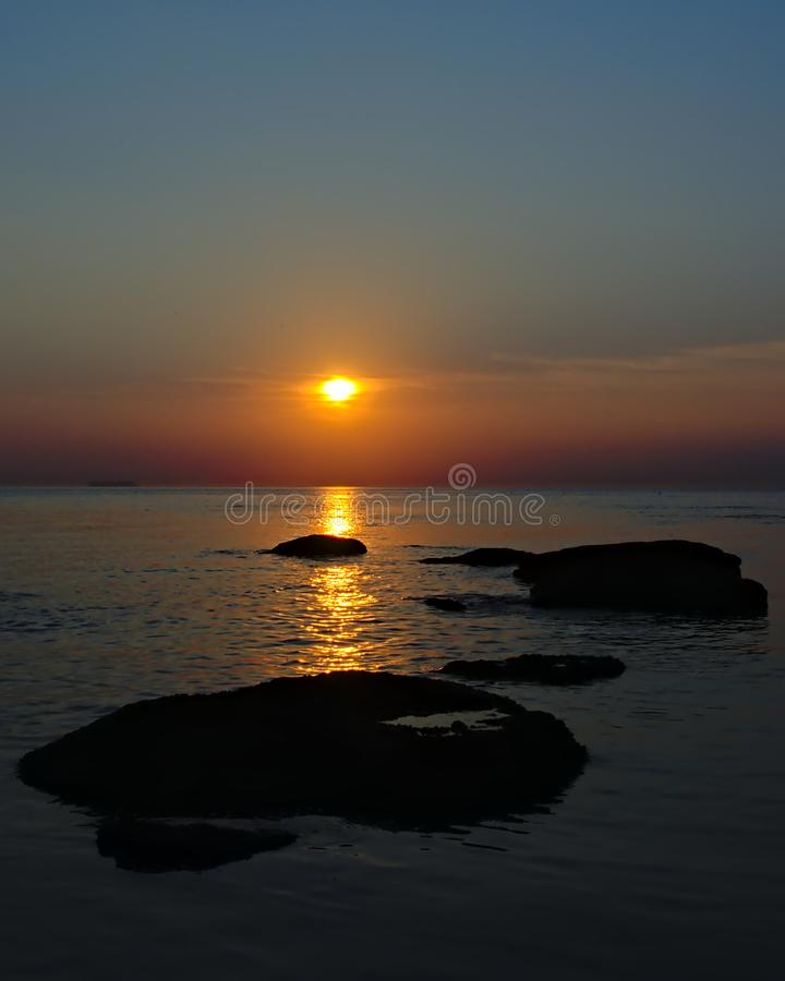Colorful sunset over the North sea with rocks in the water on the opal coast in France stock photo