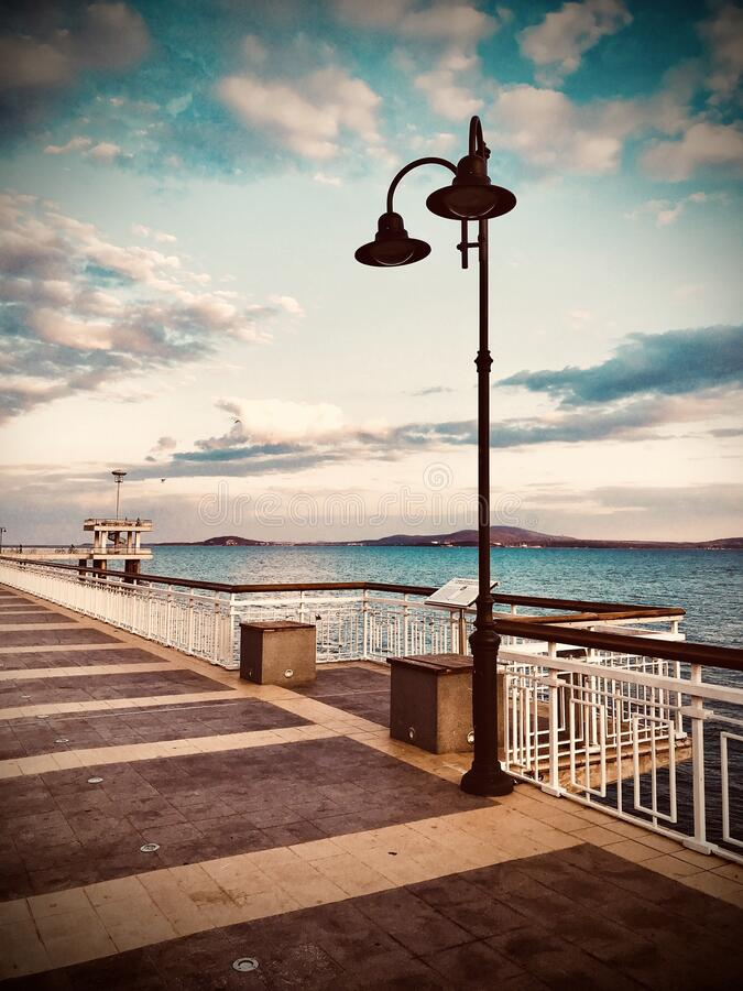 Colorful sunset over the sea bridge in Burgas bay, Bulgaria. Black Sea landscape. Vintage filter.  royalty free stock photography