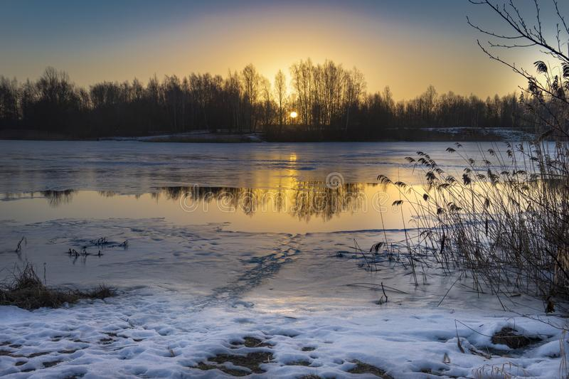 Colorful sunset over a winter lake with snow royalty free stock photos