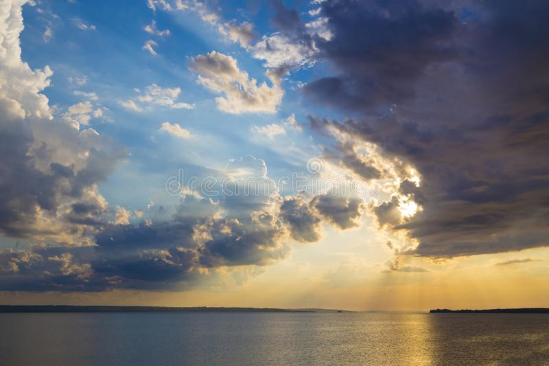 Colorful sunset on the river Dnipro. Ukraine. The rays of the sun breaking through the dark clouds. Solar path on the water stock images