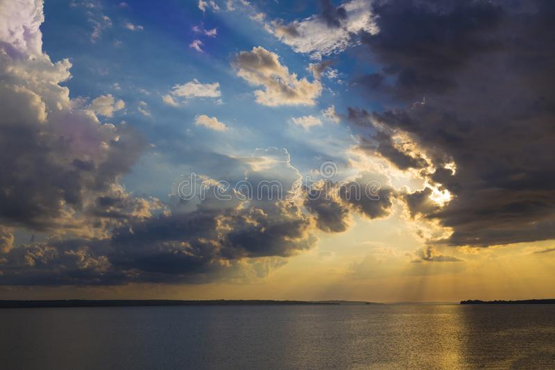 Colorful sunset on the river Dnipro. Ukraine. The rays of the sun breaking through the dark clouds. Solar path on the water. Nature landscape royalty free stock photos