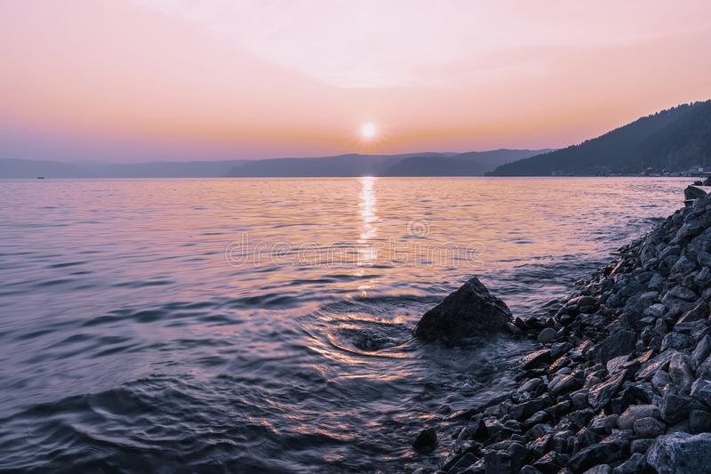 Colorful sunset on a rocky beach, late summer evening royalty free stock photo