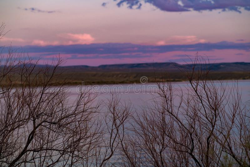 Colorful sunset in the sky through bare tree branches royalty free stock photos