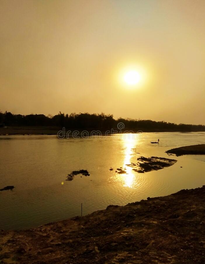 Colorful sunset sky. Image of beautiful sunset twilight sky background and reflection in a lake at Dhubri, India stock photos
