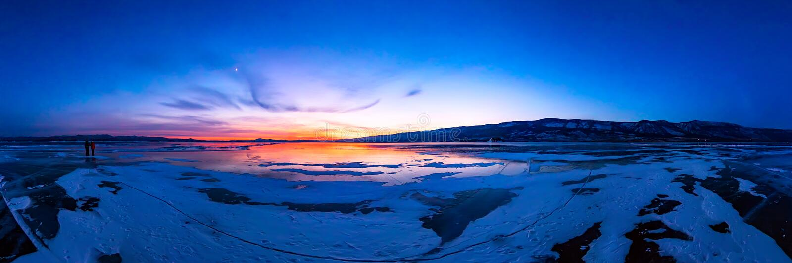 Colorful sunset on winter crack ice lake Baikal . Wide panorama stock images