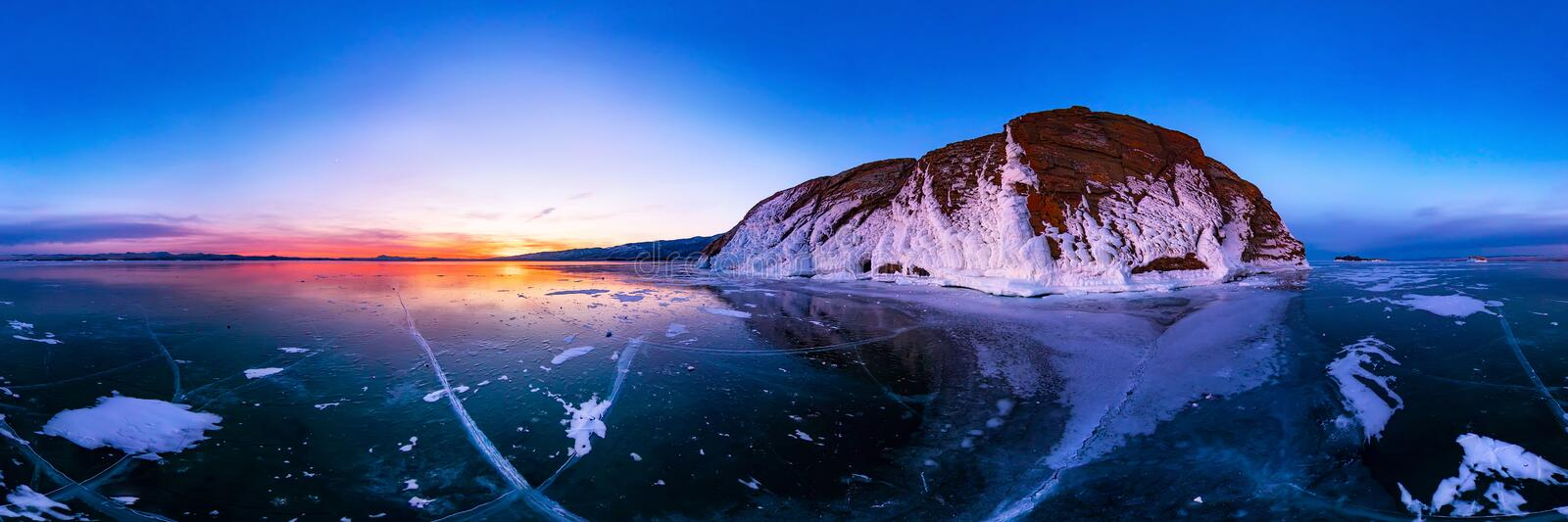 Colorful sunset on winter lake Baikal near an island covered with ice. . Cylindrical panorama 360 royalty free stock photo