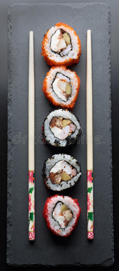 Colorful sushi with chopsticks. On a dark background royalty free stock photography