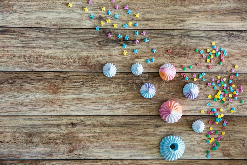 Colorful sweet homemade meringues on wooden background. Many sweet zephyrs. Trendy top view dessert image. Colorful sweet homemade meringues on wooden royalty free stock photo