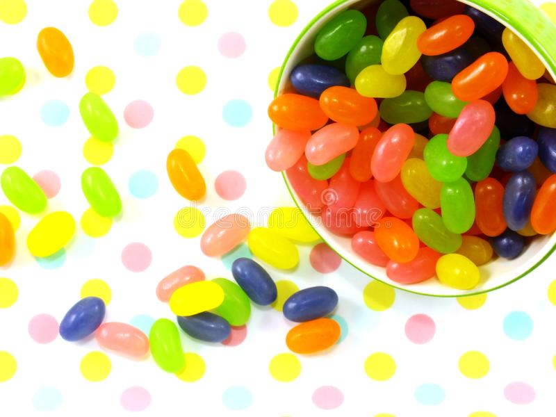 Sweet jelly beans top view on polka dot background stock photo