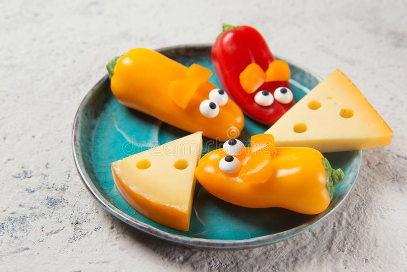 Colourful sweet mini peppers in the shape of mouses and pieces of cheese on a plate, stone table, snack for kids idea. Colourful sweet mini peppers in the shape royalty free stock images