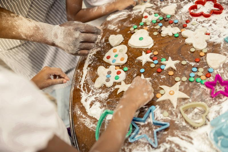Friendly family decorating their cookies with colorful sweets. Colorful sweets. Top view of friendly family decorating their cookies with colorful sweets royalty free stock photos
