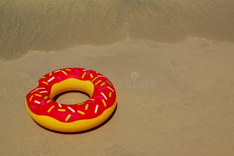 Colurful inflatable donut on the seashore. with soft wave of blue ocean in outdoor sun lighting on sandy beach. Background of travel in summer season royalty free stock photo