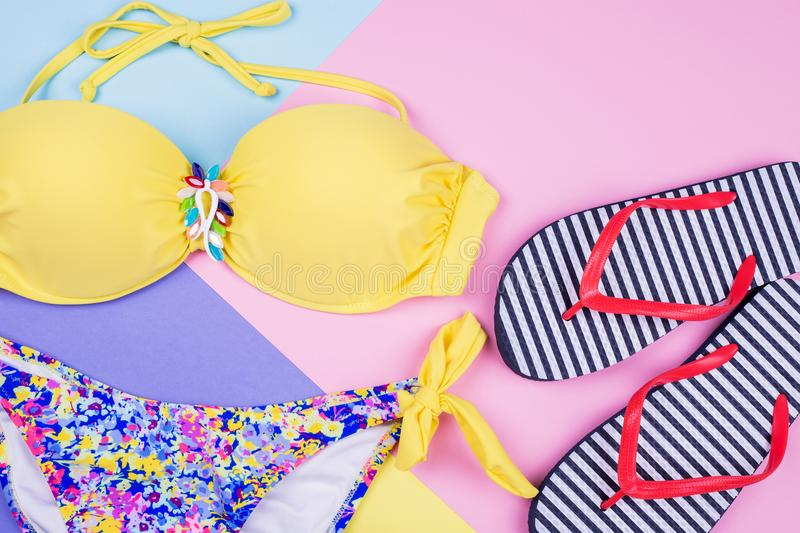 Colorful swimsuit, striped flip flops stock images
